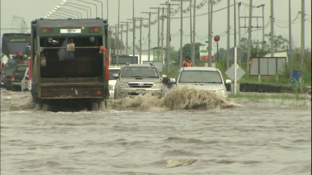 Vehicles move through flood waters on an Ayutthaya street