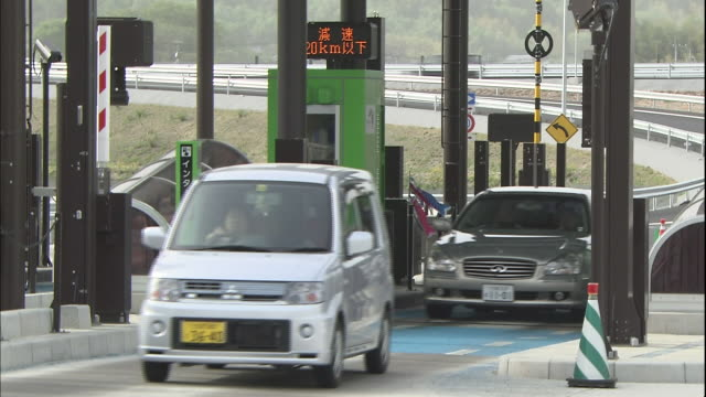 vehicles move through the electronic toll collection booths at the ashikaga interchange on the kita-kanto expressway. - boom barrier stock videos & royalty-free footage