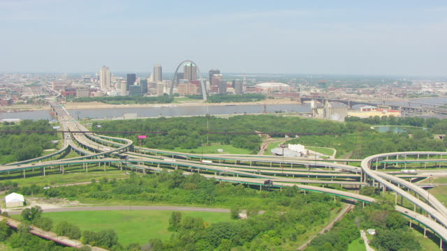 ws aerial pov vehicles moving on elevated road and street with forest area, city of st. louis and the mississippi river in background / east st. louis, st. clair county, illinois, united states - jefferson national expansion memorial park stock videos & royalty-free footage