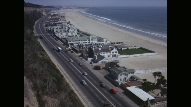 WS POV AERIAL Vehicles moving on freeway next to beach / California, United States