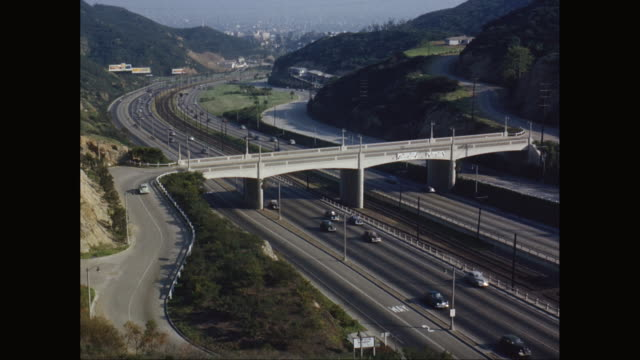 vidéos et rushes de ws vehicles moving on highway and bridge with mountain area in background / united states - route surélevée