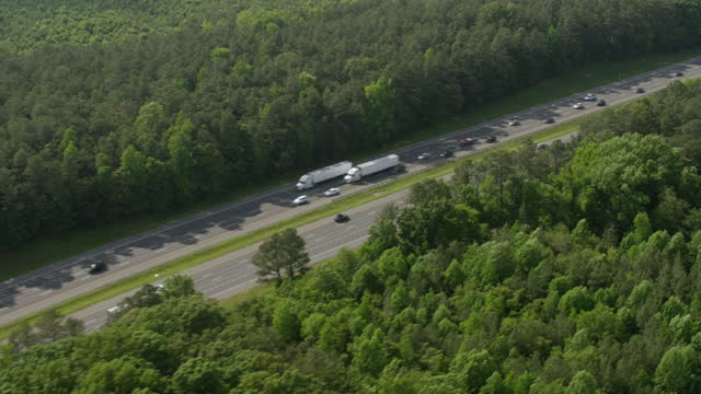 WS AERIAL POV Vehicles moving on highway through tree area/ Caroline County, Virginia, United States