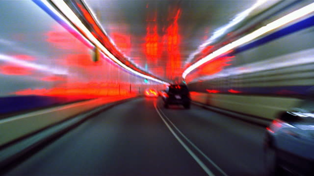 vehicles moving through tunnel into daylight - mpeg video format stock videos & royalty-free footage
