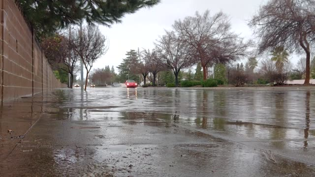 vídeos de stock, filmes e b-roll de vehicles navigating through flooded streets in clovis, california - oeste dos estados unidos