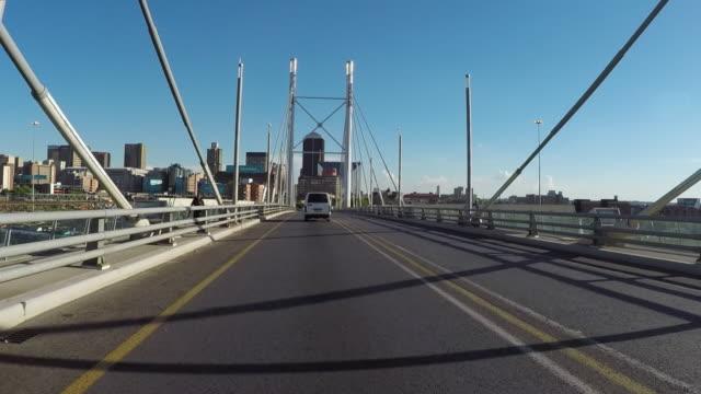 vídeos de stock e filmes b-roll de vehicles on nelson mandela bridge in city against sky on sunny day - johannesburg, south africa - joanesburgo