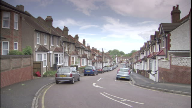 vehicles park in front of row houses in london. - villetta a schiera casa video stock e b–roll