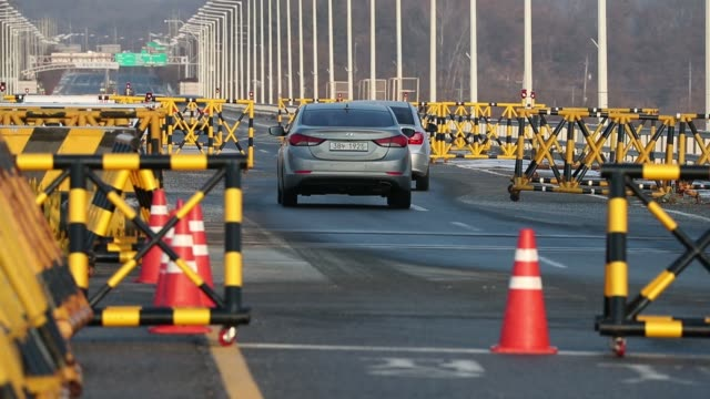 Vehicles pass a military check point on the Unification Bridge linked to North Korea near the demilitarized zone at dawn in Paju South Korea on...