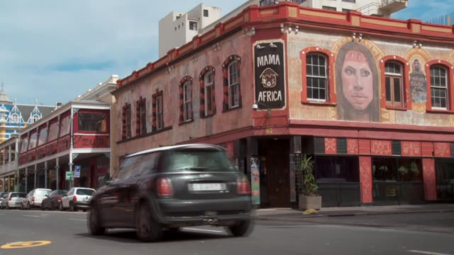 Vehicles pass by Mama Africa Restaurant on Long Street in Cape Town. Available in HD.