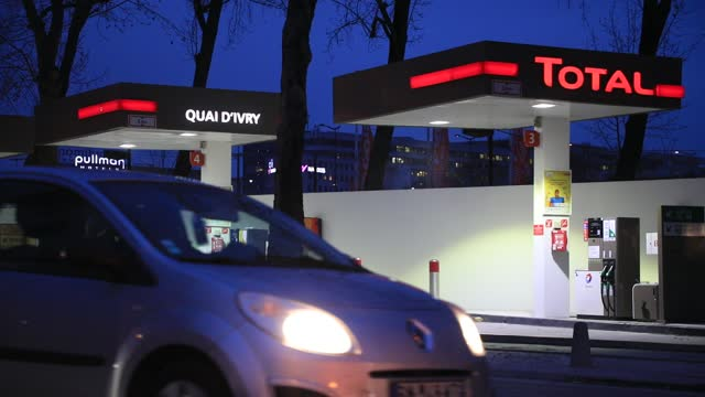 vehicles pass in front of a french oil and gas giant total brand gas station at dusk on january 20, 2021 in paris, france. the multinational total... - automobile industry stock videos & royalty-free footage