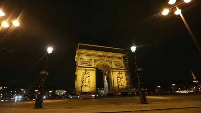 vehicles pass in front of the arc de triomphe national monument at night in paris france on tuesday feb 18 a sign for place charles de gaulle stands... - general view stock videos & royalty-free footage