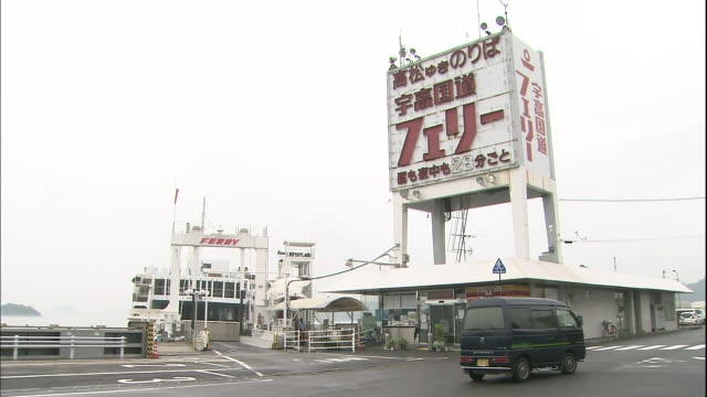 Vehicles pass one another at the ferry terminal in Uno Port in Okayama, Japan.