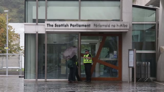 vehicles pass the scottish parliament building on a rainy day in the holyrood area of edinburgh uk on saturday sept 20 police officers speak to a... - building feature stock videos & royalty-free footage