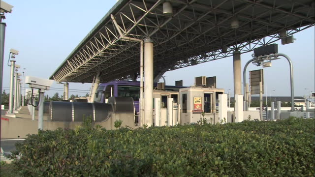 Vehicles pass through a toll gate of the access bridge to the airport / Shot on February 2 2009