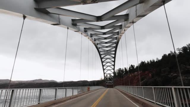 stockvideo's en b-roll-footage met een voertuig point of view shot van het rijden over cart creek bridge op flaming gorge in utah onder een bewolkte hemel - brug mens gemaakte bouwwerken
