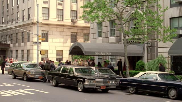 vídeos de stock, filmes e b-roll de vehicles pull up to an upscale hotel where patrons enter and pedestrians walk past - limousine