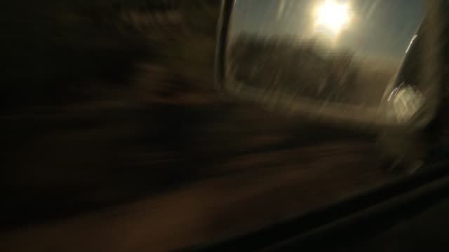 a vehicle's side mirror reflects the golden hour sun as it speeds along a desert landscape. available in hd. - golden hour stock videos & royalty-free footage