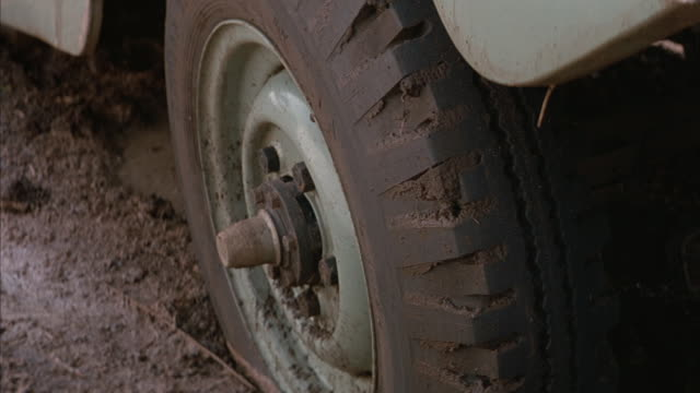 A vehicle's tire spins while stuck in mud, spraying the camera lens with mud.