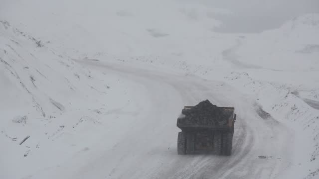 vídeos de stock e filmes b-roll de vehicles transport coal loads along a snow covered road at the raspadsky open pit mine, operated by evraz plc, in mezhdurechensk, russia, on... - caterpillar inc