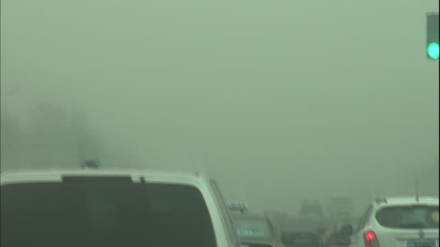 Vehicles travel along a road in Beijing shrouded in smog