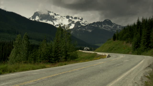 Vehicles travel along a winding mountain road. Available in HD.