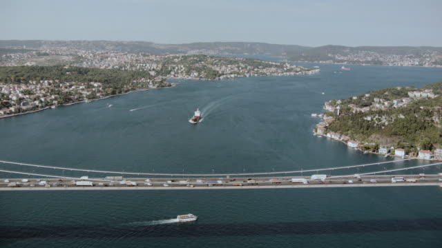 aerial vehicles traveling between europe and asia on the bosphorus bridge as boats pass beneath / istanbul, turkey - july 15 martyrs' bridge stock videos & royalty-free footage
