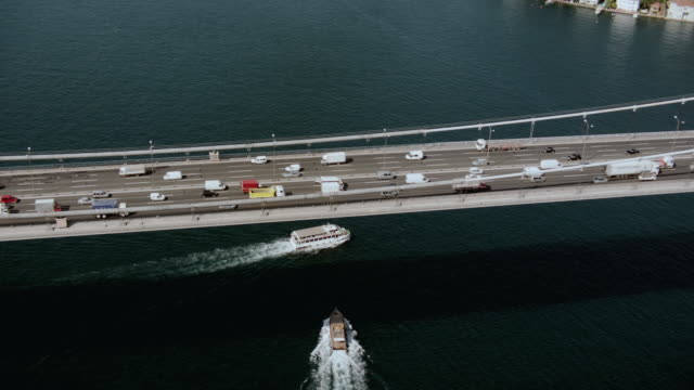 aerial vehicles traveling between europe and asia on the bosphorus bridge as boats cross the harbor / istanbul, turkey - july 15 martyrs' bridge stock videos & royalty-free footage