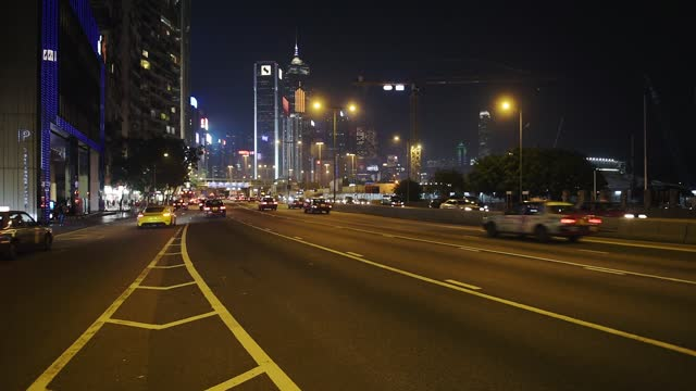 stockvideo's en b-roll-footage met vehicles traveling on the busy road in hong kong at night with scenic high-rise buildings in the background - wide shot - hong kong