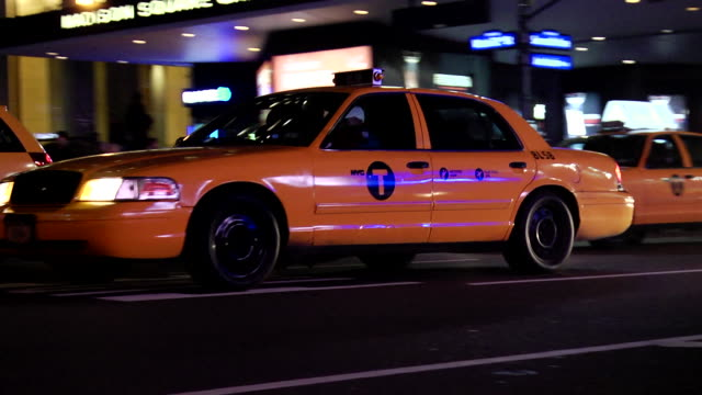 stockvideo's en b-roll-footage met vehicles w/ headlights on driving down 7th avenue parked police car madison square garden arena w/ name on venue sesame street advertisement chase... - street name sign