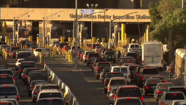 vehicles wait at a united states border checkpoint. - international border stock videos & royalty-free footage