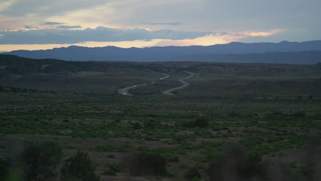 vehicles with headlights on drive on interstate 70 through the high desert of western colorado at dusk under a dramatic sky - main road stock videos & royalty-free footage