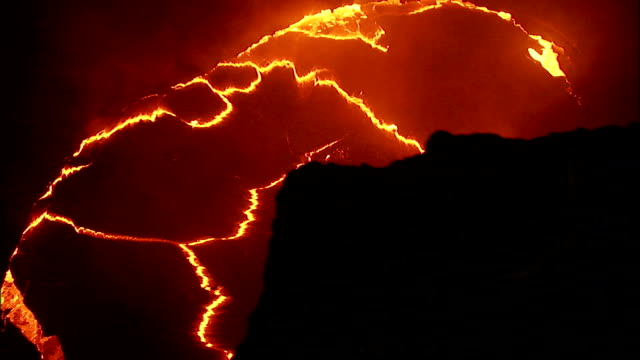 Veins of molten lava illuminate a volcano. Available in HD.