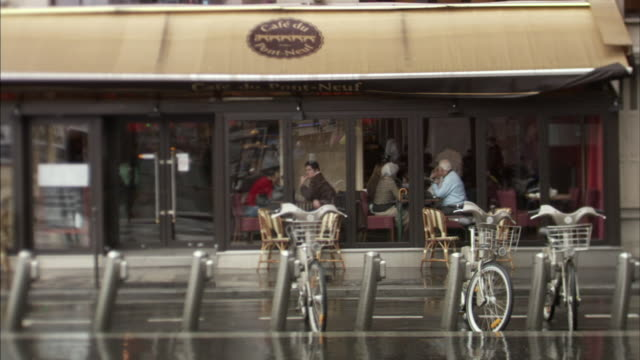 ms velib bikes on rack in front of cafe du pont-neuf in rainy day, paris, france - awning stock videos and b-roll footage