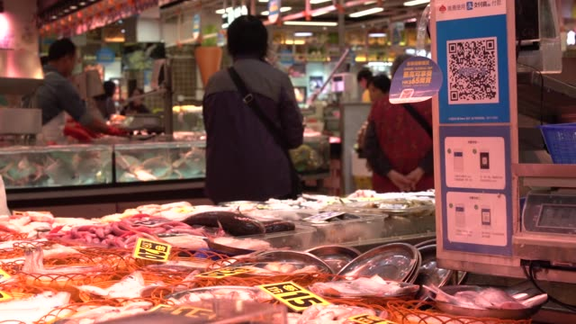 A vendor arranges fish in baskets as a merchant quick response code and payment instructions for Ant Financial Services Group's Alipay an affiliate...