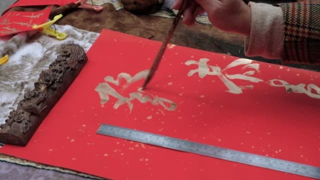vídeos y material grabado en eventos de stock de a vendor arranges papers of chinese calligraphy on decorations at a market stall ahead of lunar new year in the sheung wan district of hong kong... - sheung wan
