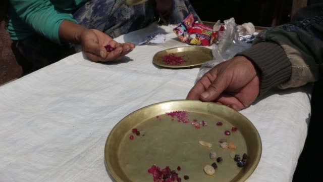 vídeos de stock e filmes b-roll de a vendor assists a customer at a gemstone market stall in mogok mandalay myanmar on monday march 14 a customer looks at gemstones on a plate at a... - jade gema