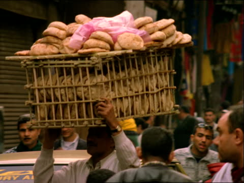 a vendor balances a load of bread on his head in a busy marketplace. - egypt stock videos & royalty-free footage