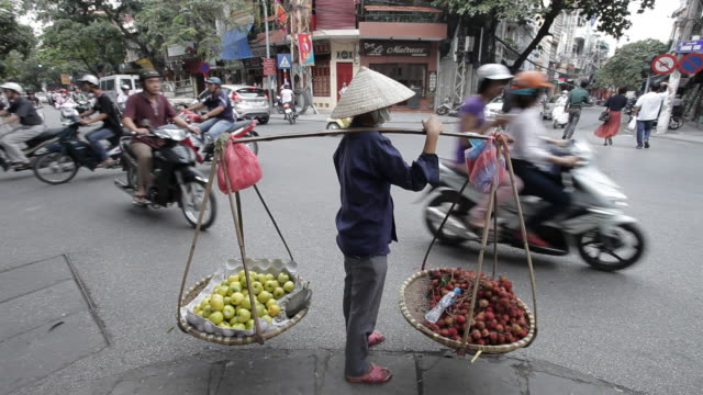 a vendor carries produce with a sway pole and watches as traffic moves through a busy intersection. - hanoi stock videos and b-roll footage