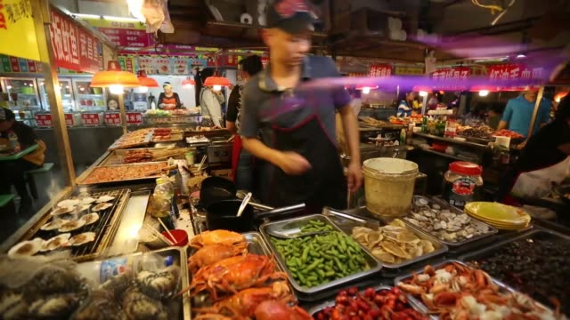 vidéos et rushes de vendor cooks at a food stall in wuhan, china, on sunday, oct. 20 food sits on display at market stall , a vendor prepares food at market stall , a... - marché établissement commercial