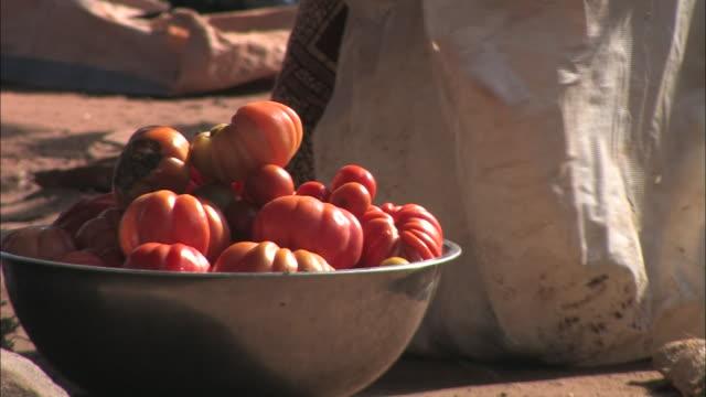vídeos y material grabado en eventos de stock de a vendor fills a bowl with orange gourds at an open air market in benin. - calabaza no comestible
