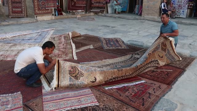 Vendor folding a rug in the inner courtyard of SherDor Madrasah in the Registan public square which was the heart of the ancient city of Samarkand in...