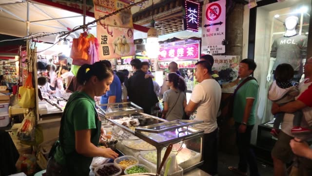 vendor grills sausages at a stall at the raohe night market in taipei, taiwan, on sunday, nov. 8 shoppers walk through the raohe night market in... - mollusc stock videos & royalty-free footage