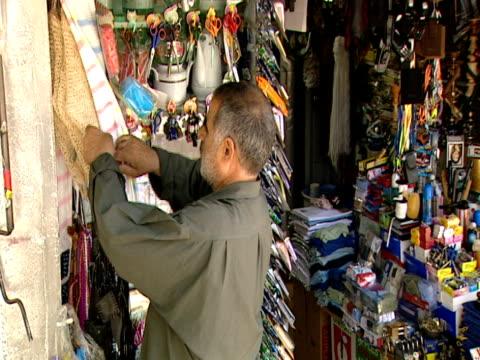 vidéos et rushes de vendor rearranges some merchandise on his market stand / tehran, iran - format vignette