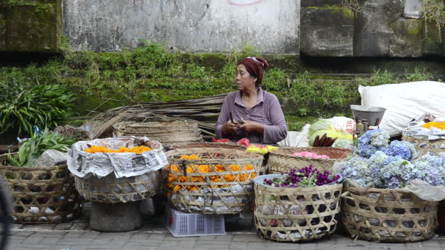 MS Vendor selling blossom for ceremony in market / Ubud, Bali, Indonesia