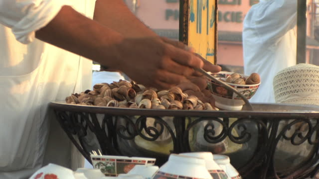 ms zi zo cu vendor selling cooked snails in djemaa el fna square, marrakech, morocco - snail stock videos & royalty-free footage