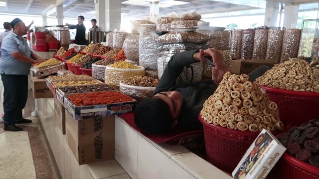 Vendor selling dried fruits nuts and seeds in Siyob Bazaar also called Siab Bazaar the largest bazaar in the city of Samarkand alternatively...