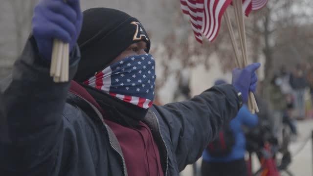 vendor sells american flags on independence avenue at the u.s. capitol on inauguration day on january 21, 2021 in washington, dc. joe biden was sworn... - 映像技法点の映像素材/bロール