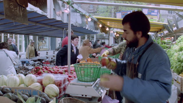 vidéos et rushes de a vendor sells fresh fruit at a street market in paris, france. - marché établissement commercial