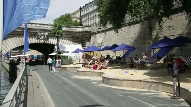 A vendor sells gelato and sorbets from a temporary hut as holidaymakers sit under parasols on the Paris Plage artificial beaches along the River...