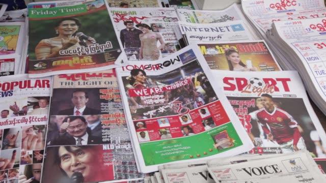 vidéos et rushes de vendor sells newspapers featuring a photograph of opposition leader leader aung san suu kyi, at a stall in yangon, myanmar, on monday, nov 9 a woman... - asiatique de l'est et du sud est