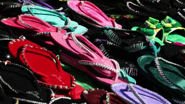 a vendor sells sandals at a stall in yangon myanmar on monday dec 18 close up sandals are displayed for sale at a stall workers handle cloths at a... - verkäufer stock-videos und b-roll-filmmaterial